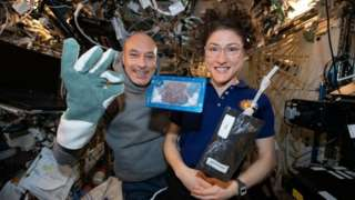 NASA of ISS commander Luca Parmitano and astronaut Christina Koch with milk and cookies on board the International Space Station
