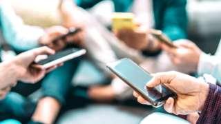 Pessoas mexendo em seus celulares