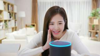Woman talking to Alexa via a smart speaker