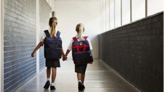 Two young girls walking hand in hand at school