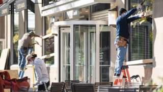 Workers board up windows at a Washington restaurant ahead of election day