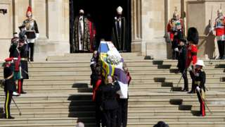 Duke of Edinburgh's coffin, covered with His Royal Highness's Personal Standard arrives at St George's Chapel carried by a bearer party found by the Royal Marines during the funeral of Prince Philip, Duke of Edinburgh at Windsor Castle on April 17, 2021 in Windsor, England.