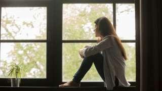 жена гледа кроз прозор