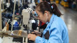 A woman sews shoes in a factory in China