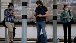 Masked passengers waiting for trains