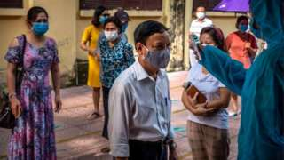 People who recently returned from Da Nang city wear face masks while queuing in safe distance to take the coronavirus disease rapid test on July 31, 2020 in Hanoi, Vietnam.