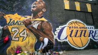 A man lights a candle in front of a Kobe Bryant mural in downtown Los Angeles on 26 January 2020