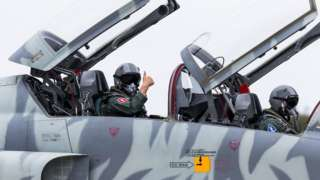 Hsiung Hou-chi (L) gives a thumbs up from aboard an F-5 fighter jet