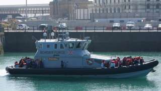 A group of people thought to be migrants are brought in to Dover, Kent, by Border Force officers, following a small boat incident in the Channel.