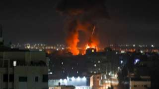 Explosions light-up the night sky above buildings in Gaza City as Israeli forces shell the Palestinian enclave,