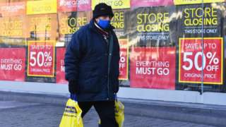 Man walking past shop with 'closing down' signs