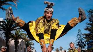 A man jumps in the air as he plays steel hand-held cymbals, called krakebs.