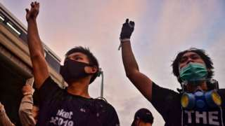 Pro-democracy protesters give the three-finger salute outside the Victory Monument BTS skytrain station in Bangkok on October 20, 2020