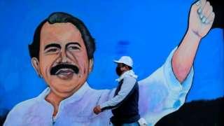 A man walks by a mural depicting Nicaraguan President Daniel Ortega, in Managua