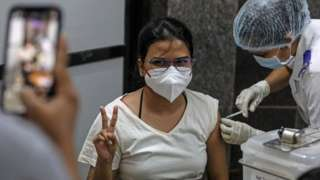 A woman gestures as she gets her first dose of a Covid-19 vaccine shot, manufactured by Serum Institute of India, inside a Vaccination Centre at Shatabdi Hospital in Mumbai, India, 12 March 2021