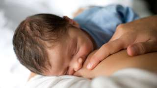 A photo of a baby being breastfed