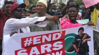 """Protesters shout slogans as they hold a banner with the inscription """"End SARS now"""""""