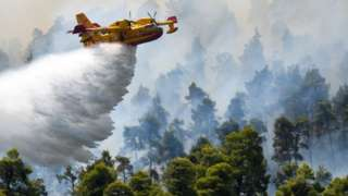 Plane drops water on Evia fires