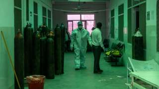 Healthcare workers in a hospital in Bijnor, Uttar Pradesh, walking past oxygen cylinders