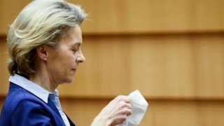 European Commission President Ursula von der Leyen puts on her mask during a debate