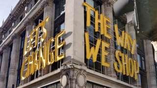 """Let's Change the way we shop"" yellow sign onside of Selfridges building"