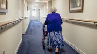 Woman with a frame in a care home