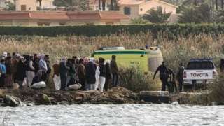 Relatives of the victims of a boat accident gather on the shore of Lake Mariout, near Alexandria, Egypt (23 February 2021)