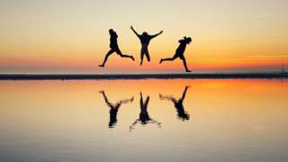 Three children jumping on West Wittering beach in West Sussex