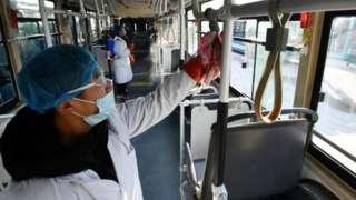 中国的防疫人员对公共汽车等交通工具消毒