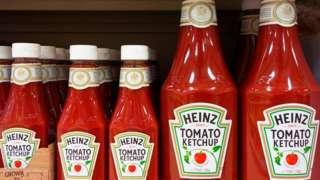 Bottles of Heinz Tomato Ketchup on a shop shelf.