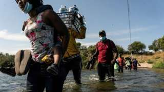 Migrants seeking asylum in the US walk in the Rio Grande river near the International Bridge between Mexico and the US as they wait to be processed, in Del Rio, Texas, on 16 September 2021