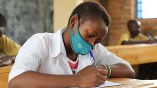Umunyeshuri w'umukobwa urimo gukora ikizamini cya leta mu Rwanda ku itariki ya 12 y'ukwezi kwa karindwi mu 2021