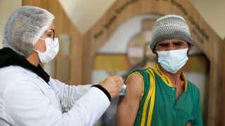 Женщина вакцинирует мужчину в Бразилии