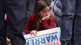 Young girl sits with Elizabeth Warren campaign sign at a New Hampshire rally, February 2020