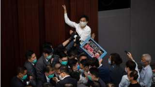 Pro-democracy lawmaker Eddie Chu Hoi-Dick (C) tries to climb a wall during a House Committee at the Legislative Council in Hong Kong, China, 08 May 2020.