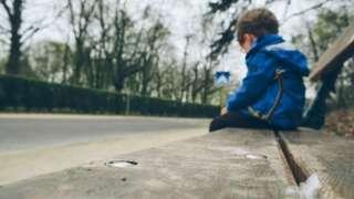 A boy sitting on a bench