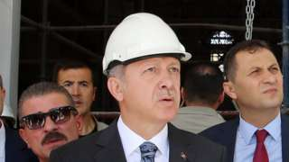 Turkish President Recep Tayyip Erdogan, wearing a construction hard hat, gazes into the middle distance squinting duringe of Ottoman Mosque in Ankara, Turkey on July 28, 2016