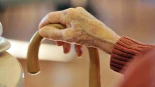 Older person's hand on walking stick