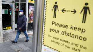 A man walks past a sign in Liverpool reminding people to keep their distance