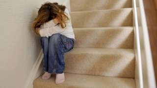 Child sitting on stairs with head in arms