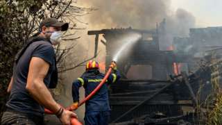 A volunteer helps firefighters put out the flames from a burning house in the Afidnes area of northern Athens on August 6 2021