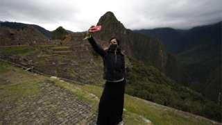 A tourist takes a selfie at Machu Picchu