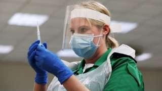 A volunteer holds a syringe