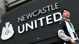 A fan waits outside the stadium prior to the Premier League match between Newcastle United and Manchester United at St. James Park