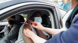 A man receives a COVID-19 vaccine at a drive-thru vaccination centre in St Albans