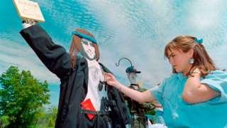 Sob céu azul, mulher olha para boneco de papelão de David Koresh