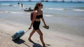 Woman with a suitcase walking along a beach