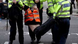 Police officers carry an Insulate Britain activist during a protest in London