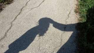 Sombra de adulto tocando em cabeca de menina