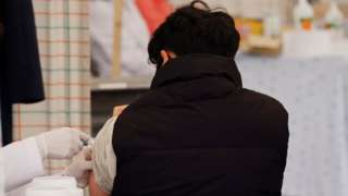 A man receives a flu jab in Seoul, South Korea